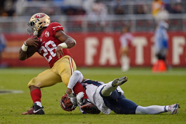 San Francisco 49ers' Carlos Hyde (28) is tackled by New England Patriots' Patrick Chung (23) while running for yardage in the second quarter of their NFL game at Levi's Stadium in Santa Clara, Calif., on Sunday, Nov. 20, 2016. (Jose Carlos Fajardo/Bay Area News Group)