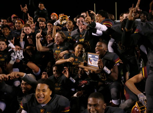 Menlo-Atherton quarterback Aajon Johnson holds the CCS trophy as he and his teammates celebrate beating Milpitas, 17-0, during the Central Coast Section Open Division I championship game at Independence High School Friday, Nov. 25, 2016, in San Jose, Calif. (Jim Gensheimer/Bay Area News Group)