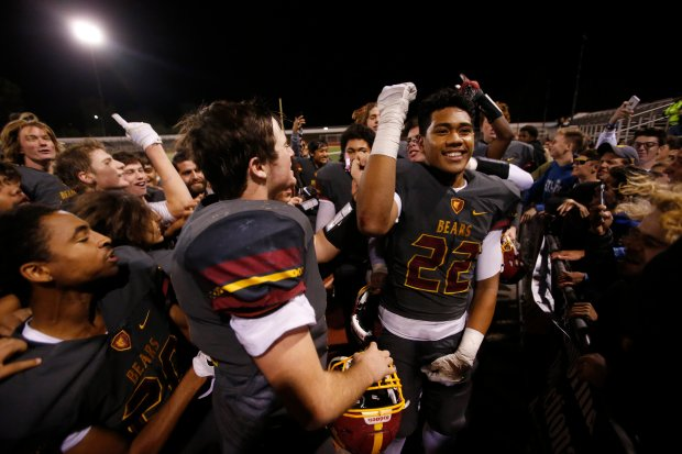 Menlo-Atherton's Daniel Heimuli (22) celebrates with teammates after beating Milpitas, 17-0, during the Central Coast Section Open Division I championship game at Independence High School Friday, Nov. 25, 2016, in San Jose, Calif. (Jim Gensheimer/Bay Area News Group)