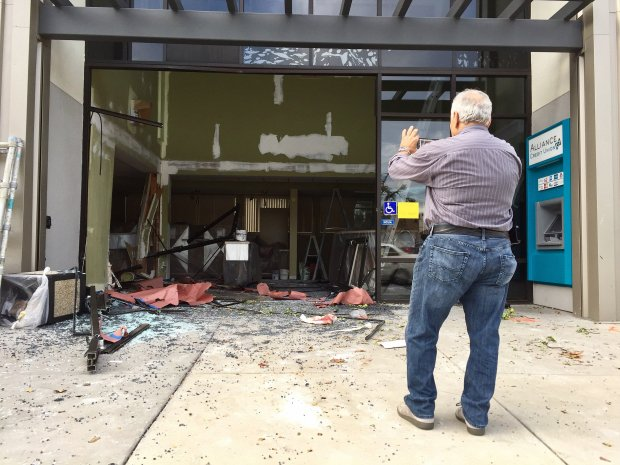 A man takes a picture of the damage caused by an SUV that crashed Friday morning into Alliance Credit Union at 265 Curtner Ave. in San Jose. A construction crew was working inside the bank at the time, and the crash killed one member and injured another, according to the San Jose Police Department. (Jason Green / Bay Area News Group)