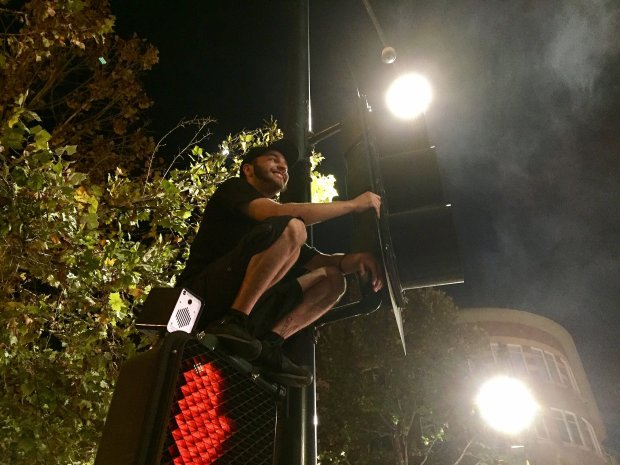 A protester perches atop a traffic signal Thursday at Fourth and San Fernando streets in downtown San Jose. (Jason Green / Bay Area News Group)