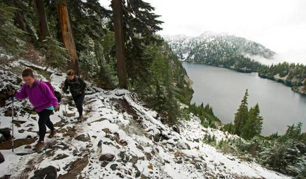 In this Nov. 3, 2015, file photo, Kasee Palmer, left, and Summer Sturhan hike on Snow Lake Trail above Snoqualmie Pass in Washington state. The far western United States set records for low snowpack levels in 2015, and a new report blames high temperatures rather than low precipitation levels. (Ted S. Warren, File AP Photo)