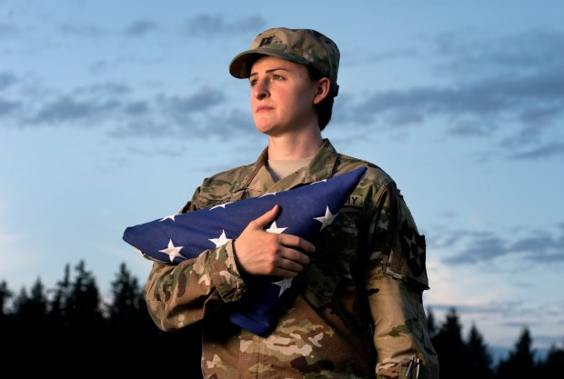 "FILE - In this Aug. 28, 2015 file photo, Capt. Jennifer Peace holds a flag as she stands for a photo near her home in Spanaway, Wash. Peace has been been deployed around the world, including Iraq and Afghanistan. When an officer suggested she leave the military rather than deal with the fallout of being a transgender soldier, Peace was taken aback. ""I couldn't believe he said that. I've been in the military for 11 years. It's everything to me. It's what I do. It's as much a part of me as anything else."" (Drew Perine/The News Tribune via AP)"