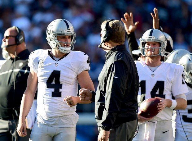 Derek Carr #4 of the Oakland Raiders talks with head coach Jack Del Rio during a video replay challenge resulting in a touchdown to Michael Crabtree #15 during the second quarter against the San Diego Chargers at Qualcomm Stadium on December 18, 2016 in San Diego, California. (Photo by Harry How/Getty Images)