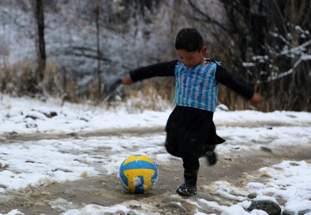 AFP PICTURES OF THE YEAR 2016In this photograph taken on January 29, 2016, Afghan boy and Lionel Messi fan Murtaza Ahmadi, 5, wears a plastic bag jersey as he plays football in Jaghori district of Ghazni province. A five-year-old Afghan boy has become an internet star after pictures went viral of him wearing an Argentina football shirt made out of a plastic bag, complete with his hero Lionel Messi's name. AFP PHOTO / AFP PHOTO / STRSTR/AFP/Getty Images