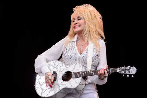 "(FILES) This file photo taken on June 29, 2014 shows US country music singer Dolly Parton on the Pyramid Stage, on the final day of the Glastonbury Festival of Music and Performing Arts on Worthy Farm in Somerset, southwest England. Wildfires raging across the US southeast are bearing down on Dollywood, the glitzy theme park founded in Tennessee by American country music legend Dolly Parton.Officials said dozens of fires are burning in the state, fanned by high winds and fueled by parched vegetation after weeks of drought.Parton released a public service announcement on November 27, 2016 urging visitors and residents of the region to exercise caution when handling fire, even as the blaze was nearing her iconic theme park. ""I love these Smoky Mountains that I call home, and I know you do too. Help protect their beauty and prevent human-caused wild fires,"" Parton, 70, says in the ad. / AFP PHOTO / LEON NEALLEON NEAL/AFP/Getty Images"