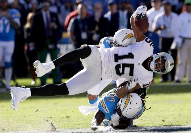 Oakland Raiders wide receiver Michael Crabtree (15) is brought down by San Diego Chargers strong safety Jahleel Addae, below, and cornerback Trevor Williams, above, during the first half of an NFL football game Sunday, Dec. 18, 2016, in San Diego. (AP Photo/Alex Gallardo)