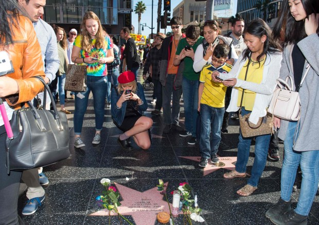 "People stop by a temporary star made by fans in tribute to actress Carrie Fisher on Hollywood Walk of Fame in Hollywood, California, on December 28, 2016.Friends, fans and Hollywood stars added their voices to a torrent of tributes for ""Star Wars"" actress Carrie Fisher, who died Tuesday at the age of 60 following a heart attack. / AFP PHOTO / VALERIE MACONVALERIE MACON/AFP/Getty Images"
