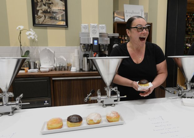 Hannah Hoffman, owner of Doughnut Dolly, has a laugh with a customer after filling an order at her business at The Market in downtown San Francisco, Calif., on Wednesday, Dec. 14, 2016. The Market follows the latest trend of food halls, mixing eateries, groceries and seating in one large space. (Dan Honda/Bay Area News Group)