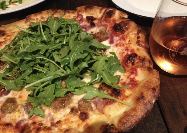 A pizza topped with lightly tossed arugula awaits diners at the Piazza deCampovida in Hopland. (Photo: Jackie Burrell/Bay Area News Group)