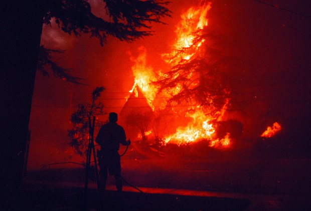 Badly over matched, an Oakland resident faces with a garden hose faces a wall of flame on Golden Gate Ave, during a firestorm in Oakland, Calif. Sunday Oct. 20, 1991. (Karl Mondon/Staff) NOTE: Scans made from negatives in 2011 for 20th anniversary project.