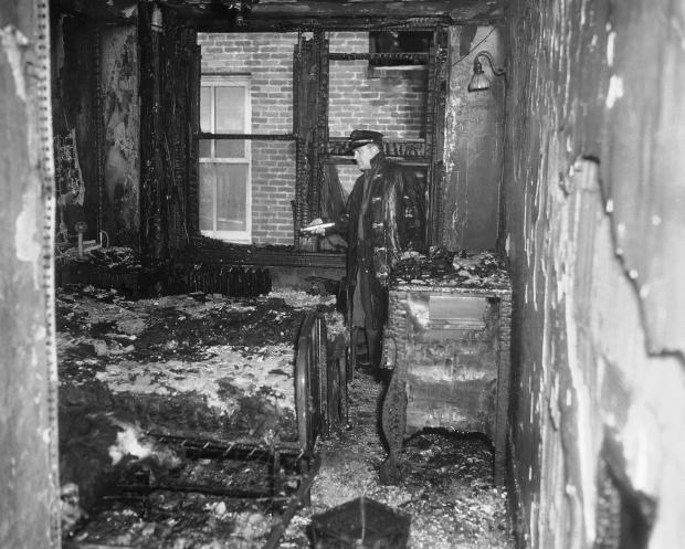 A fireman, flashlight in hand, hunts through a fire-blackened room in the Winecoff Hotel, Atlanta, Ga., Dec. 7, 1946, the scene of fire in which more than 100 persons lost their lives. Extent of the damage is shown on the charred furniture and woodwork. (AP Photo)