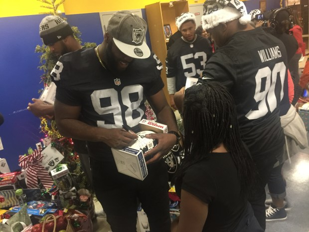 Oakland Raiders defensive end Branden Jackson signs a football for a member of the East Oakland Boys and Girls Club. (Courtney Cronin/Bay Area News Group)
