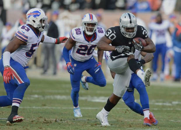 The Oakland Raiders' SaQwan Edwards (30) powers for extra yardage against the Buffalo Bills in the second half of their NFL game at the Oakland Coliseum in Oakland, Calif., on Sunday, Dec. 4, 2016. (Dan Honda/Bay Area News Group)