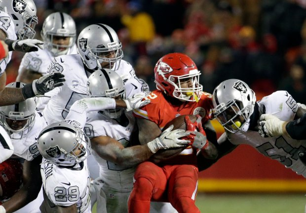 Kansas City Chiefs running back Spencer Ware (32) is tackled by Oakland Raiders linebacker Bruce Irvin, right, and others, during the second half of an NFL football game in Kansas City, Mo., Thursday, Dec. 8, 2016. The Kansas City Chiefs won 21-13. (AP Photo/Charlie Riedel)