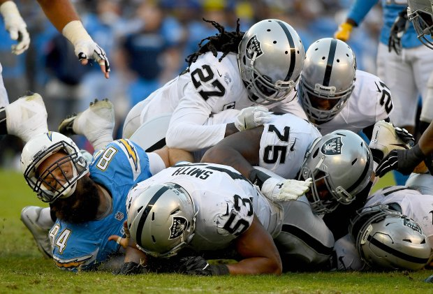 SAN DIEGO, CA - DECEMBER 18: Malcolm Smith #53 of the Oakland Raiders recovers fumble by Kenneth Farrow #27 of the San Diego Chargers while teammate Sean McGrath #84 looks on en route to the Raiders 19-16 win over Chargers at Qualcomm Stadium on December 18, 2016 in San Diego, California. (Photo by Donald Miralle/Getty Images)