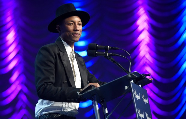 "Pharrell Williams presents the award for ensemble performance to the cast of ""Hidden Figures"" at the 28th annual Palm Springs International Film Festival Awards Gala on Monday, Jan. 2, 2017, in Palm Springs, Calif. (Photo by Chris Pizzello/Invision/AP)"
