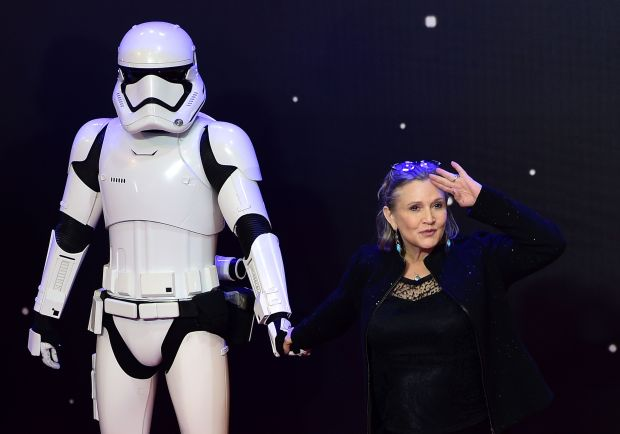 "(FILES) This file photo taken on December 16, 2015 shows US actress Carrie Fisher (R) posing with a storm trooper as she attends the opening of the European Premiere of ""Star Wars: The Force Awakens"" in central London.A family spokesman for the said December 27, 2016 that Carrie Fisher, the iconic actress who portrayed Princess Leia in the Star Wars series, died Tuesday following a massive heart attack last week. She was 60. / AFP PHOTO / LEON NEALLEON NEAL/AFP/Getty Images"