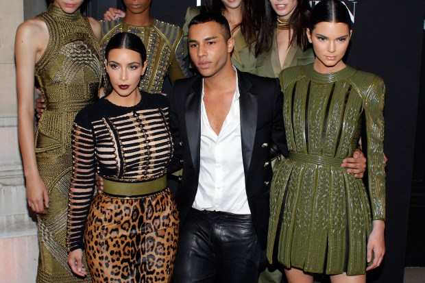 Fashion designer Olivier Rousteing, center, Kim Kardashian, left, and her sister Kendall Jenner pose prior to attend the Vogue party, in Paris, Wednesday July 9, 2014. (AP Photo/Thibault Camus)