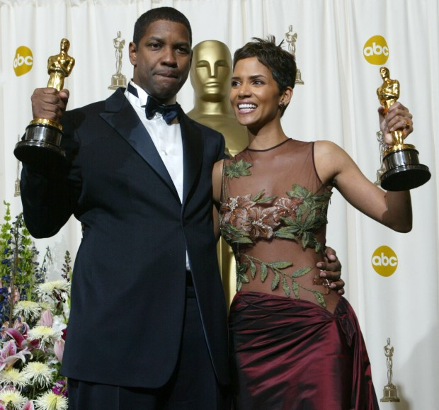 "402719 186: Best Actor and Actress winners Halle Berry and Denzel Washington pose with their awards backstage during the 74th Annual Academy Awards March 24, 2002 at The Kodak Theater in Hollywood, CA. Berry, who won for ""Monster's Ball"", is the first African-American woman to ever win an Oscar for a leading role. Washington won for his role in ""Training Day"". (Photo by Frederick M. Brown/Getty Images)"