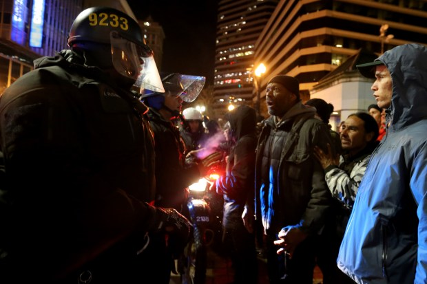 Protesters argue with Oakland Police officers after man was arrested during a protest against the inauguration of Donald Trump in Oakland, Calif., on Friday, Jan. 20, 2017. (Ray Chavez/Bay Area News Group)