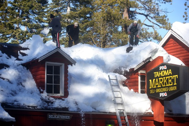Workers remove snow from the roof of the Tahoma Market on Monday, Jan. 30, 2017, in Tahoma, Calif. (Aric Crabb/Bay Area News Group)