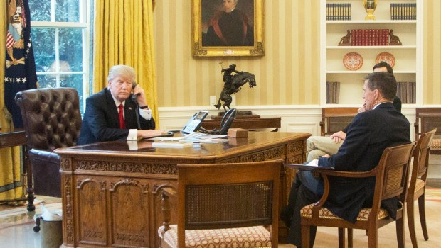 President Donald Trump, left, accompanied by National Security Adviser Michael Flynn, right, and Senior Advisor to the President Jared Kushner, speaks on the phone with King of Saudi Arabia Salman bin Abd al-Aziz Al Saud in the Oval Office at the White House in Washington, Sunday, Jan. 29, 2017. (AP Photo/Manuel Balce Ceneta)