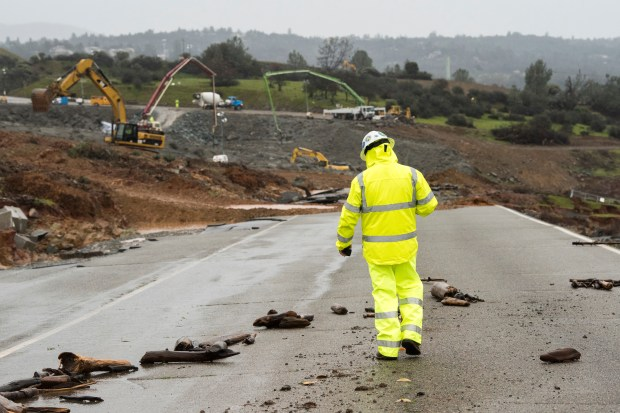 A worker walks down the damaged roadway near the Oroville Dam emergency spillway. Last weekend overflow waters from the emergency spillway eroded much of the area below the spillway. The California Department of Water Resources continues to examine and repair the erosion with more than 125 construction crews working around the clock, and placing 1,200 tons of material on the spillway per hour using helicopters and heavy construction equipment at the Butte County site. Photo taken February 17, 2017. Brian Baer/ California Department of Water Resources
