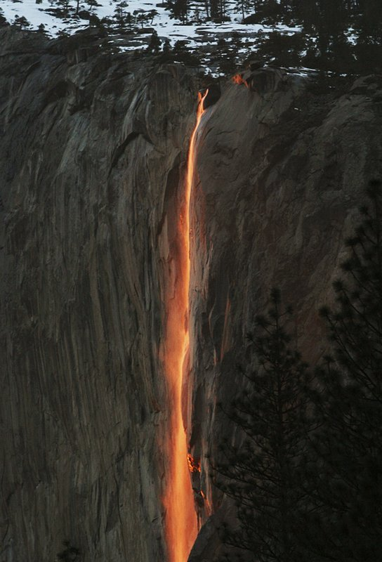 "In this Feb. 16, 2010, file photo, a shaft of sunlight creates a glow near Horsetail Fall, in Yosemite National Park, Calif. Mother Nature is again putting on a show at California's Yosemite National Park, where every February the setting sun draws a narrow sliver on a waterfall to make it glow like a cascade of molten lava. The phenomenon known as ""firefall"" draws scores of photographers to the spot, which flows down the granite face of the park's famed rock formation, El Capitan. (Eric Paul Zamora/The Fresno Bee via AP, File)"