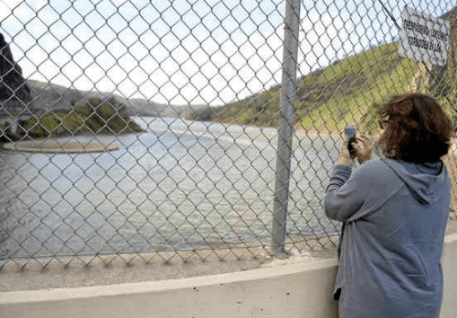 Dianna Englebrecht of Napa takes a picture with her mobile phone of the Lake Berryessa Glory Hole as the water approaches the top of the spillway. (Joel Rosenbaum — The Reporter)