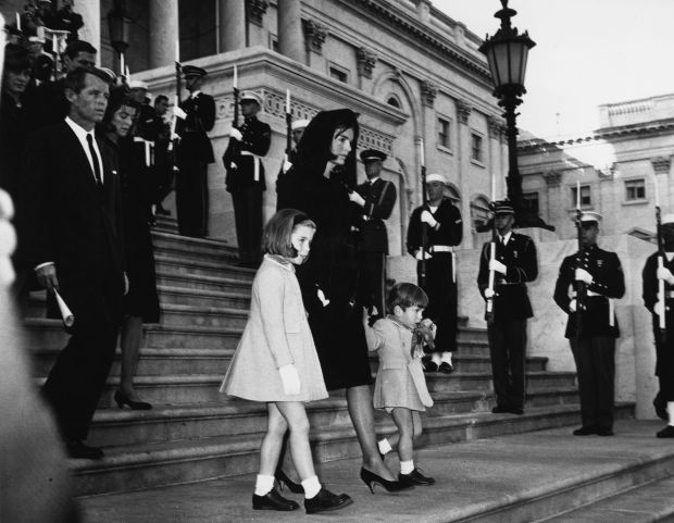 Jackie Kennedy (1929 - 1994) and her children John Jr. (1960 - 1999) and Caroline, walking down steps past a guard of honour at the funeral of President Kennedy. Robert Kennedy is following them. (Photo by Central Press/Getty Images)