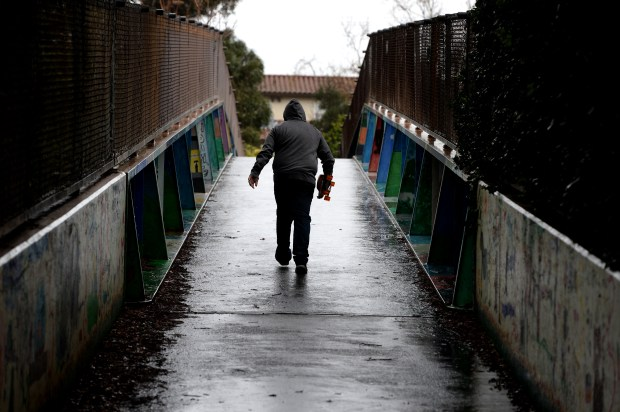 A skateboarder walks on the footbridge over Highway 17 in Los Gatos, Calif., on Friday, Feb. 17, 2017. The morning hours brought light, but steady rain to the area. (Dan Honda/Bay Area News Group)