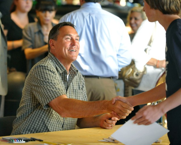 Former San Francisco 49er Dwight Clark, shakes hands with one of the many fans attending a promotional event for the new Madden NFL 12 video game at a Safeway grocery store in San Ramon, Calif., on Tuesday, Aug. 30, 2011. The Madden NFL 12, made by game developer EA Sports, is available at the Blockbuster Express DVD machine located inside Safeway. (Doug Duran/Staff)