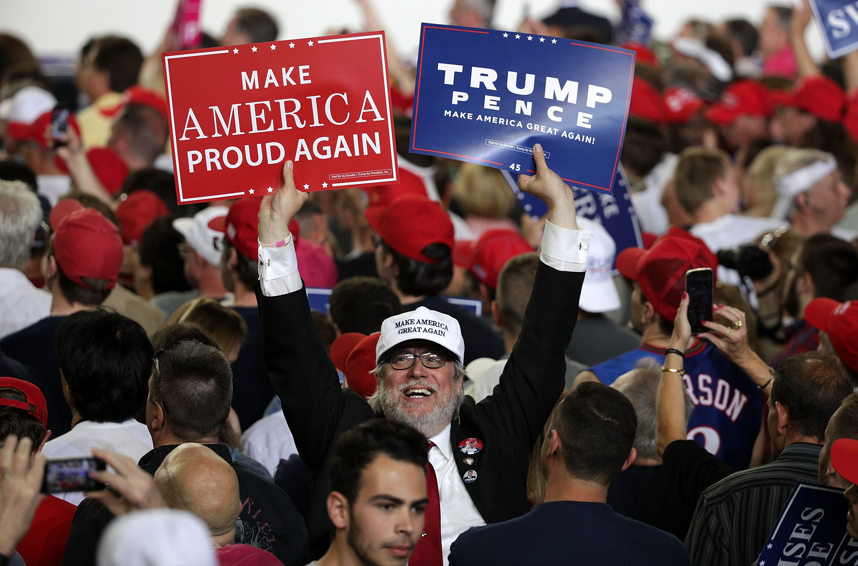 "A supporter holds up signs during a ""Make America Great Again Rally"" at the Pennsylvania Farm Show Complex & Expo Center April 29, 2017 in Harrisburg, Pennsylvania. President Trump held a rally to mark his first 100 days of his presidency.  (Photo by Alex Wong/Getty Images)"