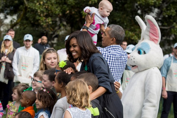 WASHINGTON, DC - MARCH 28: First lady Michelle Obama poses for a photo with a group of children as President Barack Obama lifts up a child during the annual White House Easter Egg Roll on the South Lawn of the White House March 28, 2016 in Washington, DC. The tradition dates back to 1878 when President Rutherford B. Hayes allowed children to roll eggs on the South Lawn. (Photo by Drew Angerer/Getty Images)