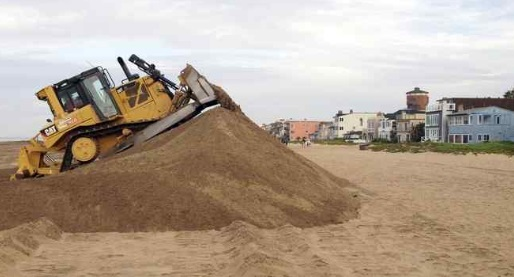 A bulldozer piles sand into a high berm to protect homes along Sunset Beach in Huntington Beach. (AP Photo/Michael R. Blood, File)