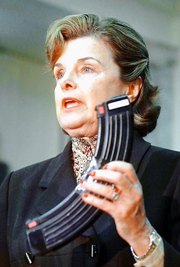Sen. Dianne Feinstein, D-Calif., holds a gun magazine as she calls for a debate on gun control measures during a press conference on Capitol Hill, on May 6, 1999. (AP Photo/Khue Bui)