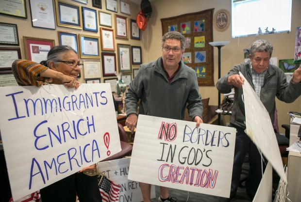 Day Worker Center volunteers, from left, Marilu Delgado, 64, Dave Arnone, 54, and Job Lopez, 72, display the signs that they'll use for the May Day rallies at the Day Worker Center of Mountain View in Mountain View, Calif., on Wednesday, April 26, 2017. (LiPo Ching/Bay Area News Group)