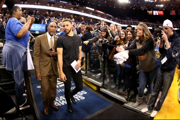 Golden State Warriors' Stephen Curry (30) wears street clothes as he walks with chief of security Ralph Walker before the game against the New Orleans Pelicans in the first half of an NBA game at Oracle Arena in Oakland, Calif., on Saturday, April 8, 2017. While Curry recovers from a bruised left knee, Kevin Durant returned to play after recovering from a knee injury that occurred on February 28. (Ray Chavez/Bay Area News Group)
