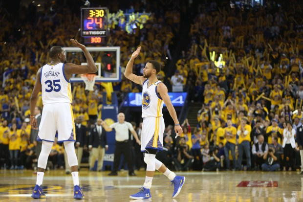 The Golden State Warriors' Stephen Curry (30) high-fives Kevin Durant (35) against the Portland Trail Blazers in the third quarter of Game 1 of their NBA first round playoff series at Oracle Arena in Oakland, Calif., on Sunday, April 16, 2017. (Ray Chavez/Bay Area News Group)