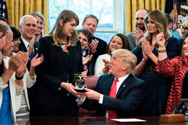 US Vice President Mike Pence (L) and US First Lady Melania Trump (R) watch as US President Donald Trump presents National Teacher of the Year Sydney Chaffee, of Massachusetts, with an award during a national teacher of the year event in the Oval Office of the White House April 26, 2017 in Washington, DC. / AFP PHOTO / Brendan Smialowski (Photo credit should read BRENDAN SMIALOWSKI/AFP/Getty Images)