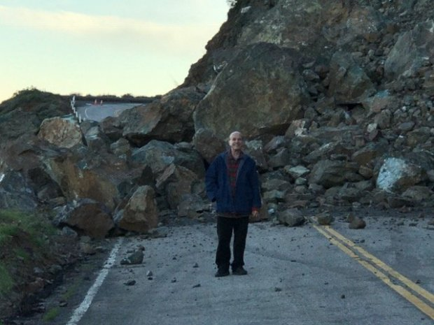 Brother Benedict of New Camaldoli Hermitage poses in front of one ofthe landslides on Highway 1 near the monastery in Big Sur in February 2017. Road damage caused by winter storms blocked access to the monastery, which sits in the hills at the end of a two-mile road. (Photo courtesy of New Camaldoli Hermitage) We have permission to use this image online and to share it with sister publications.