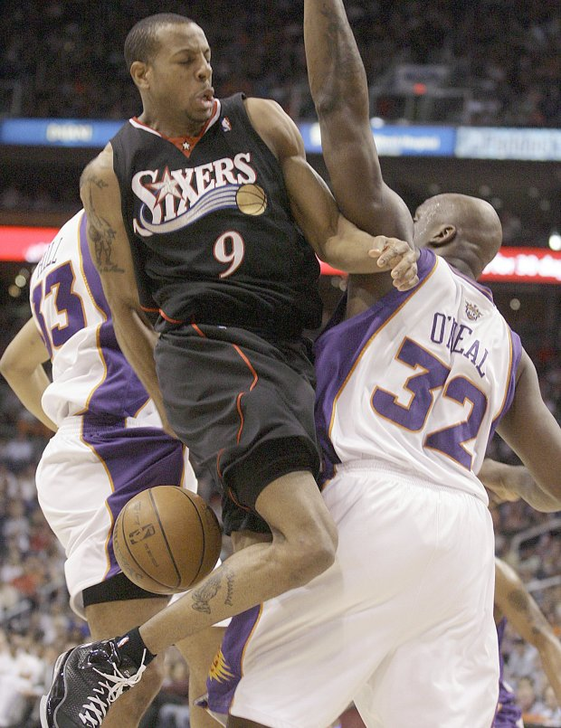 Philadelphia 76ers guard Andre Iguodala, center, attempts a behind-the-back pass as he collides with Phoenix Suns center Shaquille O'Neal, right, and forward Grant Hill, left, in the first quarter of an NBA basketball game Saturday, March 1, 2008, in Phoenix.(AP Photo/Paul Connors)