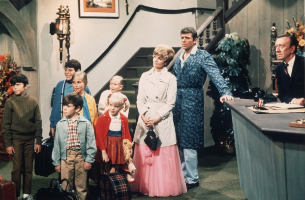 American actors Robert Reed and Florence Henderson stand in a hotel lobby with their television family in a still from the TV series 'The Brady Bunch,' circa 1969. (L-R) Christopher Knight, Barry Williams, Mike Lookinland, Maureen McCormick, Eve Plumb, Susan Olsen, Henderson, Reed, unidentified. (Photo by Paramount Television/Courtesy of Getty Images)