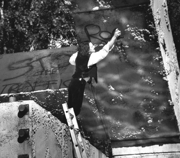 """Bono, from the Irish rock band 'U2', spray paints """"Rock 'n Roll"""" on a concrete fountain sculpture in San Francisco, CA, Nov. 12, 1987, during a surprise concert that attracted an estimated 20,000 people. (AP Photo/Ken Howard)"""
