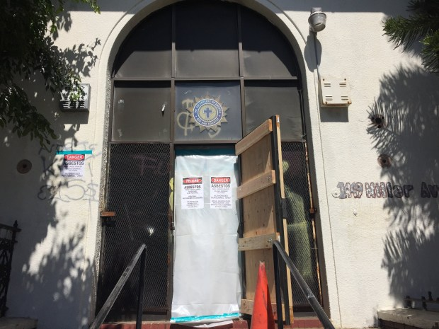 The front door of the old Oakland city library building at 1449 Miller Ave. shows asbestos warning signs which went up May 18, 2017. The building has been hit by two fires this spring. May 18, 2017. (David DeBolt/Bay Area News Group)