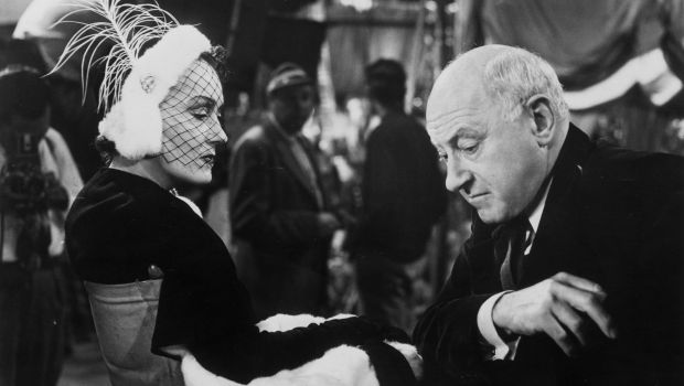 Film actress Gloria Swanson (1897-1983) and film director Cecil B. DeMille (1881-1959) sitting together on the set of 'Sunset Boulevard,' a biting satire on Hollywood stardom in which DeMille plays himself, 1949. (Photo by Hulton Archive/Getty Images)