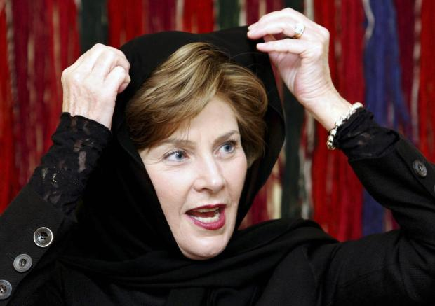 US First Lady Laura Bush tries on a headscarf given to her by Saudi doctor Samia al-Amudi (unseen) during a meeting with cancer survivors in Jeddah, 24 October 2007. Bush started a visit to Kuwait today, her third stop in a Middle East tour aimed at promoting awareness of breast cancer and restoring Washington's image in the region. AFP PHOTO/POOL/Hasan JAMALI (Photo credit should read HASAN JAMALI/AFP/Getty Images)