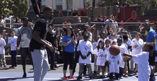 Warriors star Durant plays with a kid on a basketball court he refurbished at Lincoln Park in Oakland. May 17. 2017