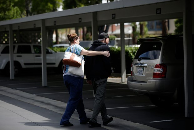 Medical assistant caregiver Amanda McGehee walks Steve Williams to the car to go over to the Alzheimer's Activity Center, where Williams is in respite care during the day, on Wednesday, May 24, 2017. Williams was diagnosed with early onset Alzheimer's disease seven years ago. (Josie Lepe/Bay Area News Group)